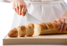 Female cook cutting bread Royalty Free Stock Image