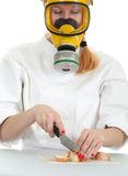 Female cook cutting onion in gas mask Stock Images