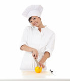 Female cook cutting paprika and speaking on the ph Royalty Free Stock Image