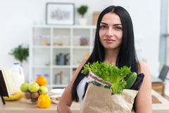 Female cook holding bag full of greens, just came back from market, ready to prepare healthy food with cookbook recipe Stock Photos