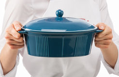 Female cook holding blue ceramic pan Royalty Free Stock Photography