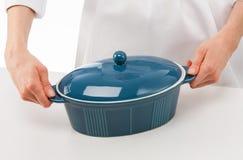 Female cook holding blue ceramic pan Stock Photos