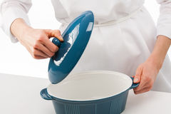 Female cook holding lid above blue ceramic pan Stock Photo