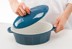 Female cook holding lid above blue ceramic pan Stock Photos