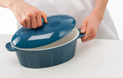Female cook holding lid above blue ceramic pan Stock Image