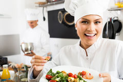 Female cook holding plate with green salad. Female cook wearing uniform holding plate with green salad Stock Photo