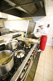 Female cook in kitchen. A female cook working in an industrial kitchen, standing at a large frying pan, making pancakes. Motion blur applied stock photography