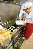 Female cook in kitchen. A female cook working in an industrial kitchen, standing at a large frying pan, making pancakes. Motion blurred applied on her busy hands Royalty Free Stock Images
