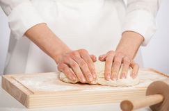 Female cook kneading dough Royalty Free Stock Photos