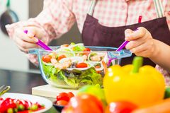 Female cook making fresh shrimp salad in her home cooking, vario. Us vegetables on table, showing her hand holding utencils mixing the salad, close up with Royalty Free Stock Photo