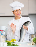 Female cook preparing big fish Royalty Free Stock Photos