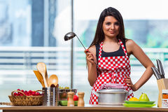 The female cook preparing soup in brightly lit kitchen Royalty Free Stock Photo