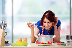 The female cook preparing soup in brightly lit kitchen Stock Image