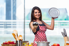The female cook preparing soup in brightly lit kitchen Royalty Free Stock Photography