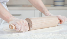 Female cook rolling out dough on  the table Royalty Free Stock Image