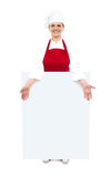 Female cook showing white blank ad board Royalty Free Stock Image