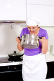 Female cook smelling her recipe in the pot Stock Image