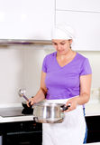 Female cook smelling her recipe in the pot Stock Photos