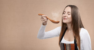 Female cook smells a steaming spoon Stock Image