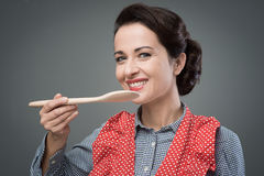 Female cook tasting a recipe. Smiling female cook tasting a recipe with a wooden spoon Stock Photos