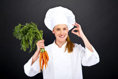 Female cook in white uniform with bunch of carrots Royalty Free Stock Photo