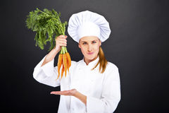 Female cook in white uniform with bunch of carrots Royalty Free Stock Photos