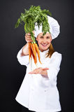 Female cook in white uniform with bunch of carrots Stock Images