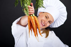 Female cook in white uniform with bunch of carrots Royalty Free Stock Image