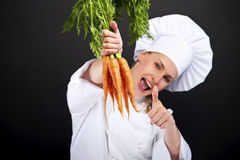 Female cook in white uniform with bunch of carrots Royalty Free Stock Photography