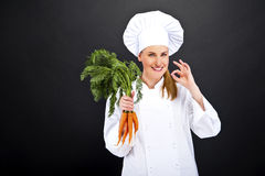 Female cook in white uniform with bunch of carrots Stock Photos