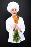 Female cook in white uniform with bunch of carrots Royalty Free Stock Images