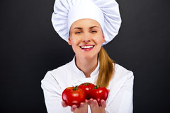 Female cook in white uniform with tomatoes Royalty Free Stock Photo
