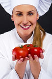 Female cook in white uniform with tomatoes Stock Photo