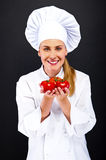 Female cook in white uniform with tomatoes Royalty Free Stock Photography
