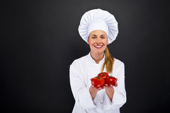 Female cook in white uniform with tomatoes Royalty Free Stock Images