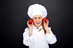Female cook in white uniform with tomatoes Royalty Free Stock Image