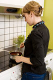 Female Cooking Supper in Kitch. A female is cooking supper on the stove in her apartment Royalty Free Stock Images