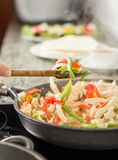 Female cooking vegetables and chicken in pan stock photo