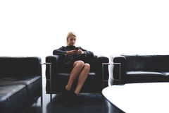 Female with cool style is chatting in social networks via cell telephone while sitting in waiting room indoors,. Attractive blonde hair woman reading text Royalty Free Stock Photography