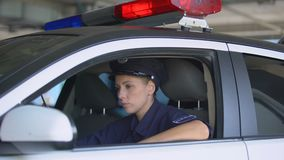 Female cop talking on walkie-talkie, responding emergency call, crime prevention. Stock footage stock footage