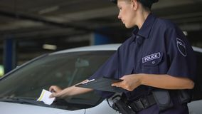 Female cop writing traffic ticket and putting on windshield, parking violation. Stock footage stock video footage