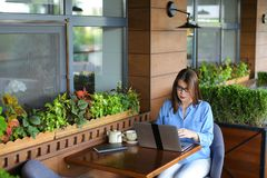 Female copywriter typing article by laptop at restaurant. Female copywriter typewriting article by laptop at cafe. Pretty girl sitting in arm chair near window Royalty Free Stock Photos