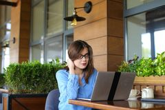 Female copywriter typing article by laptop at restaurant. Female copywriter typewriting article by laptop at cafe. Pretty girl sitting in arm chair near window Royalty Free Stock Photo