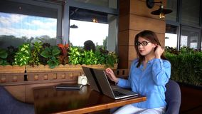 Female copywriter typing article by laptop at restaurant. Female copywriter typewriting article by laptop at cafe. Pretty girl sitting in arm chair near window Stock Photos