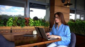 Female copywriter typing article by laptop at restaurant. Female copywriter typewriting article by laptop at cafe. Pretty girl sitting in arm chair near window Royalty Free Stock Image