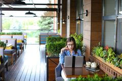Female copywriter typing article by laptop at restaurant. Female copywriter typewriting article by laptop at cafe. Pretty girl sitting in arm chair near window Stock Photography