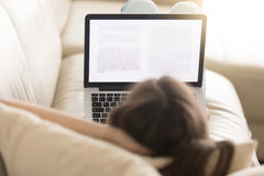 Female copywriter working with text on coach. Close up photo of woman lying on sofa with laptop on knees reads electronic book. Female freelancer copywriter Royalty Free Stock Photo