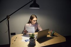 Female corporate manager comparing data in document with busines. Millennial businesswoman looking on screen of laptop and comparing new data with business plan stock image