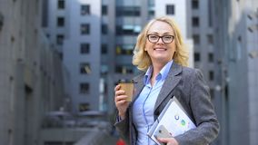 Female corporate worker breathing free holding coffee cup and work documents. Stock footage stock video