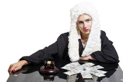 Female corrupt judge with gavel and money at table. Isolated on white Royalty Free Stock Images